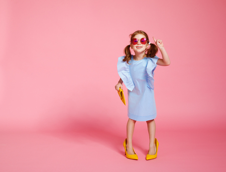 funny child girl fashionista in big mothers yellow shoes on colored background