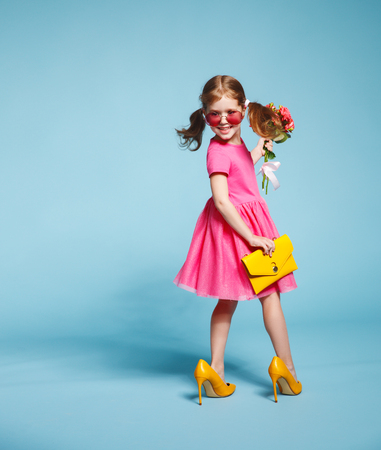 funny child girl fashionista in big mother's yellow shoes on colored background 免版税图像