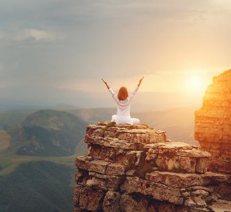 woman practices yoga and meditates   on mountains, peak Stock fotó - 101297317