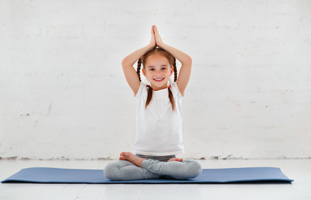 child girl doing yoga and gymnastics in the gym
