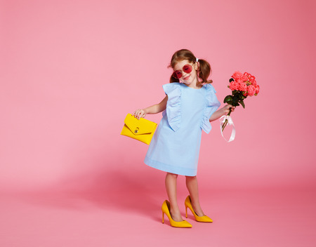 funny child girl fashionista in big mother's yellow shoes on colored background Archivio Fotografico