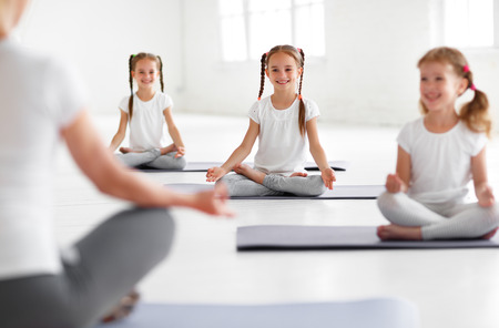 children practicing yoga in a lotus pose with a teacher