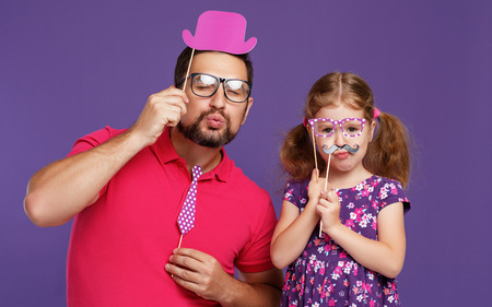 happy fathers day! funny dad and daughter with mustache fooling around on colored purple background  Stok Fotoğraf