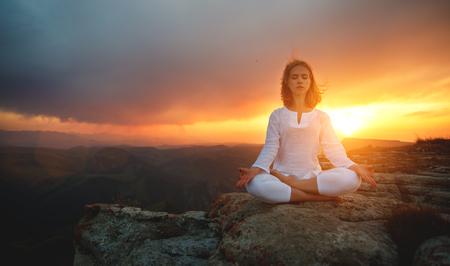 woman practices yoga and meditates   on mountains, peak