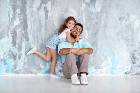 Fathers day. Happy family daughter hugging dad and laughs near an empty wall