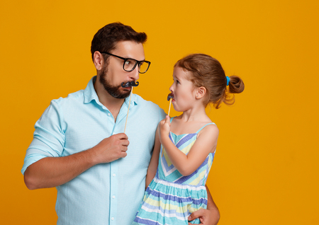 happy fathers day! funny dad and daughter with mustache fooling around on colored yellow background