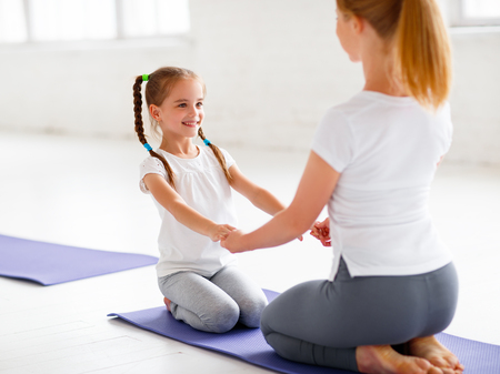 mother with child practicing yoga in a lotus pose