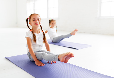 children girls doing yoga and gymnastics in the gym