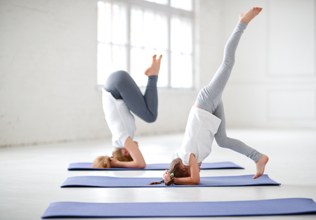 mother with child practicing yoga in a headstand