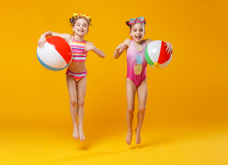 funny funny happy children in bathing suits and swimming glasses jumping on colored background Stock Photo