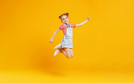 Grappig kind meisje springen op een gekleurde gele achtergrond Stockfoto - 102568647