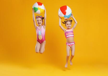 lustige lustige glückliche Kinder in Badeanzügen und Schwimmbrillen, die auf farbigem Hintergrund springen