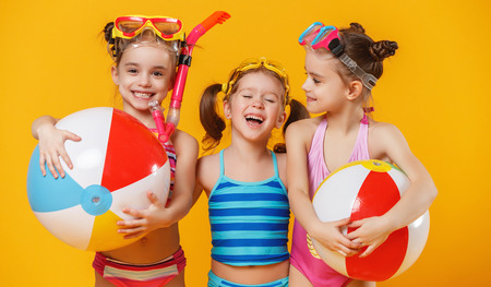 funny funny happy children in bathing suits and swimming glasses jumping on colored background  Stockfoto