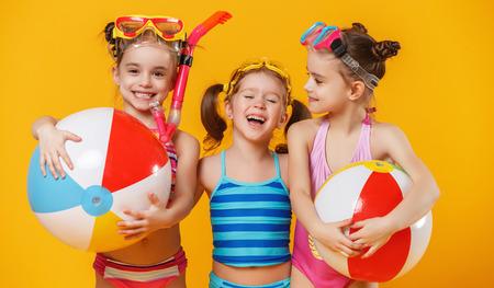 Grappige grappige gelukkige kinderen in badpakken en zwemglazen springen op gekleurde achtergrond Stockfoto - 102568864