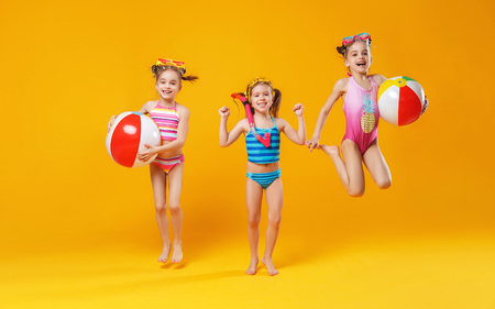 funny funny happy children in bathing suits and swimming glasses jumping on colored background  版權商用圖片
