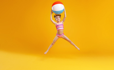 funny happy child   jumping in swimsuit and swimming glasses on colored background  Фото со стока