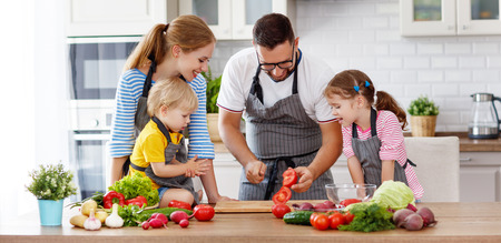 happy family with children preparing vegetable salad at home Imagens - 102568936