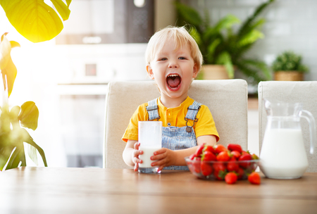 happy baby boy eating strawberries with milk at home Stock Photo