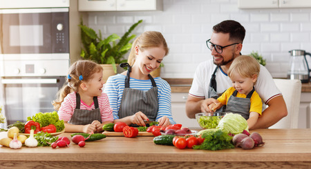 Happy family with child  preparing vegetable salad at home