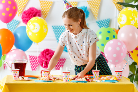 Woman prepares for holiday, sets   table for children's birthday Archivio Fotografico - 103907081