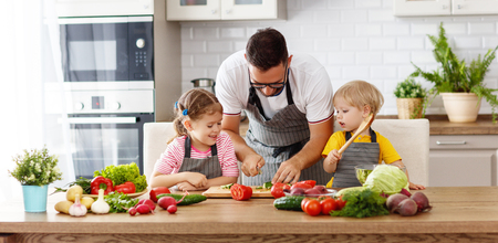 Father with children preparing vegetable salad at home