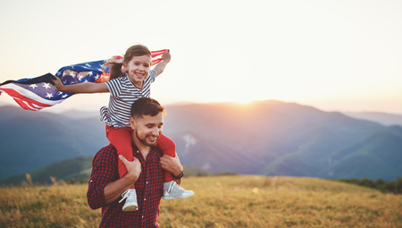 Happy family father and child with flag of united states enjoying sunset on nature 免版税图像