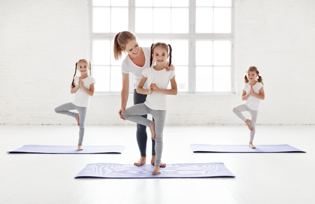 Children practicing are engaged in gymnastics and yoga with  teacher 스톡 콘텐츠