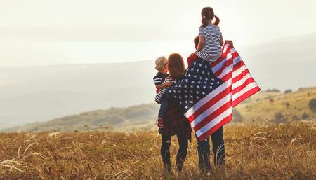 Familia feliz con la bandera de América, EE.UU. al atardecer al aire libre Foto de archivo