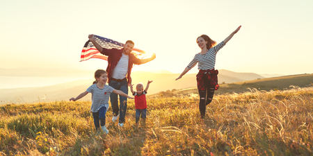 happy family with the flag of america USA at sunset outdoors
