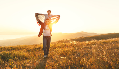 happy family father and child with flag of united states enjoying sunset on nature