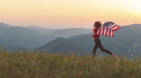young happy woman with flag of united states enjoying the sunset on nature Фото со стока - 103969535