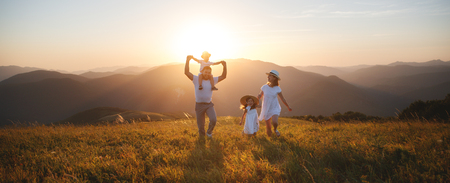 Héhé: mère, père, fils d'enfants et fille sur la nature au coucher du soleil