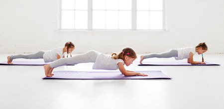 children girls doing yoga and gymnastics in the gym Banco de Imagens - 105557361