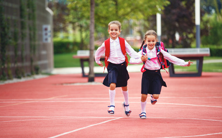 Happy children girls girlfriend schoolgirl student elementary school Standard-Bild