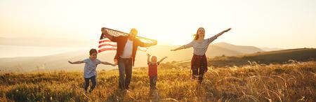 gelukkige familie met de vlag van Amerika VS bij zonsondergang buitenshuis