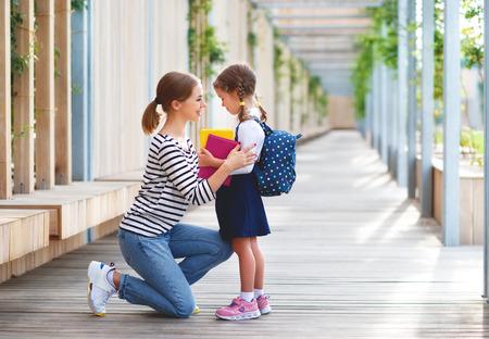 premier jour à l'école. mère mène une petite écolière enfant en première année