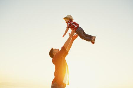 Dia del padre. Padre de familia feliz e hijo pequeño jugando y riendo en la naturaleza al atardecer Foto de archivo - 105557641