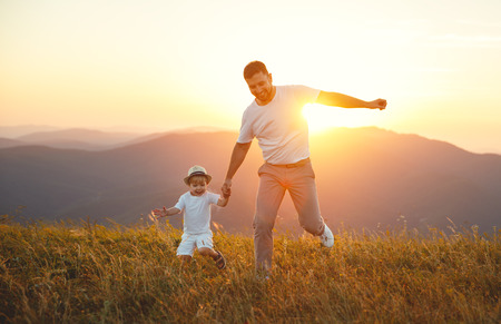 Fathers day. Happy family father and toddler son playing and laughing on nature at sunset Фото со стока