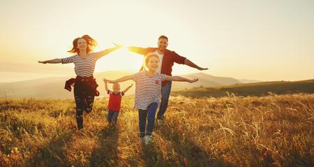 Gelukkige familie: moeder, vader, kinderen zoon en dochter op natuur op zonsondergang Stockfoto - 105557667