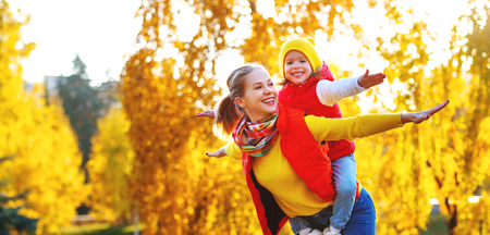 happy family mother and child daughter playing and laughing on   autumn walk Standard-Bild