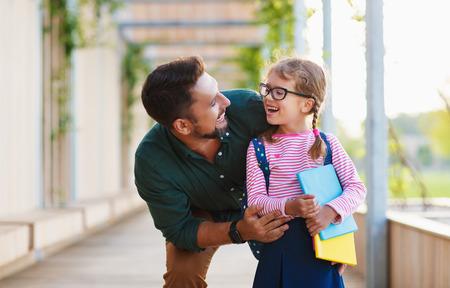 premier jour à l'école. père mène une petite écolière enfant en première année
