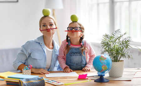 funny mother and child daughter doing homework writing and reading at home