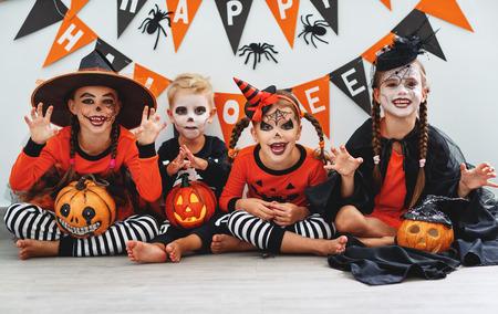 Fröhliches Halloween! eine Gruppe von Kindern in Anzügen und mit Kürbissen zu Hause