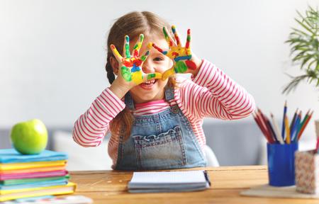 Happy funny child girl dessine en riant montre les mains sales avec de la peinture Banque d'images