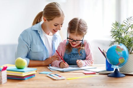 mother and child daughter doing homework writing and reading at home