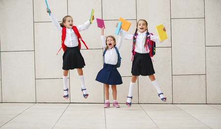 Happy children girls girlfriend schoolgirl student elementary school Foto de archivo