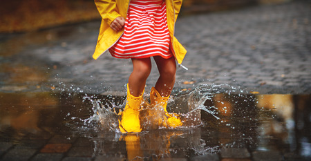 happy child in yellow rubber boots  in puddle on an autumn walk Banque d'images - 107007299