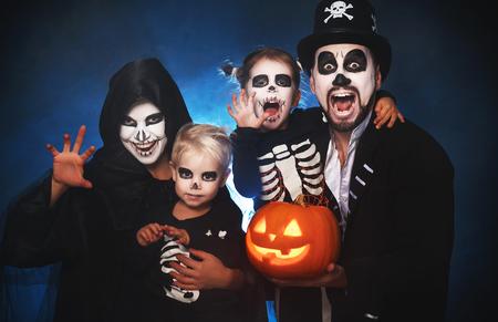 Feliz madre de familia, padre e hijos en disfraces y maquillaje en una celebración de Halloween Foto de archivo