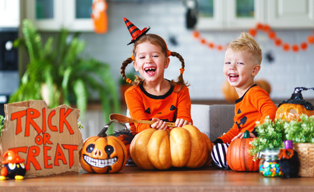 happy children in costumes of pumpkins are preparing the home for holiday Halloween