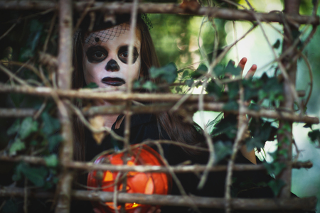 Happy Halloween! horrible creepy child girl in  witch costume with a pumpkin in forest